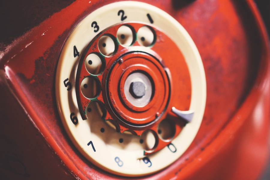 Closeup photo of an old rotary dial on a bright red telephone