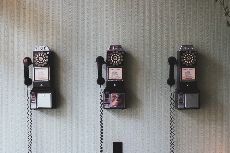 Three vintage rotary payphones hanging on a wall